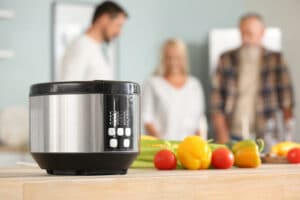 Modern multi cooker with fresh vegetables on table in kitchen