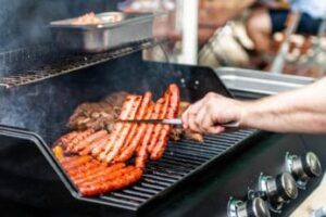 a-person-grilling-steaks-and-sausages