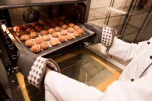 a-person-taking-pastries-out-of-an-oven