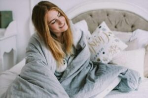 a smiling woman sitting on a bed