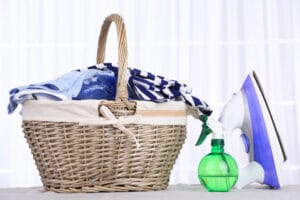basket of clothes, spray bottle, and flatiron on table