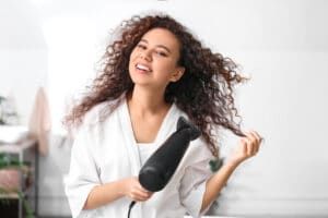 beautiful young woman blow drying curly hair