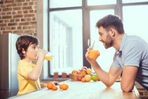 father and son drinking juice