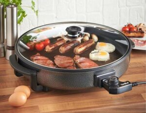 frying eggs, meat, tomatoes, and sausages