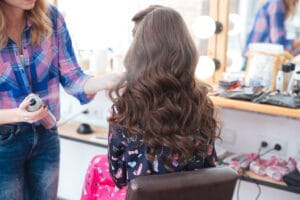 Hairdresser applying hairspray for long curly hair of woman