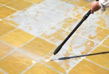 man hand cleaning outdoor driveway