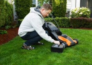 man-putting-a-battery-in-his-lawn-mower