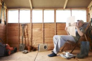 man-reading-the-paper-in-his-garden-shed