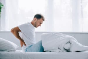 man suffering from back pain while sitting on bed