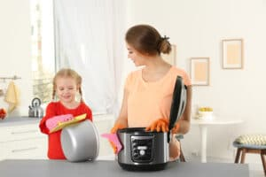 mother and daughter wiping pots
