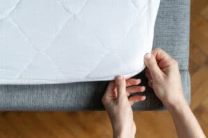 top view of hand putting on mattress topper on couch