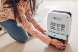 woman-changing-water-container-of-dehumidifier