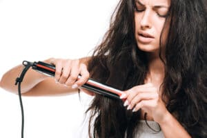 woman-upset-while-using-straightening-iron