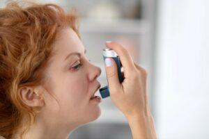 woman using inhalator while having an asthma attack