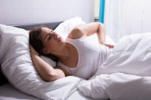 young woman unable to sleep due to back pain