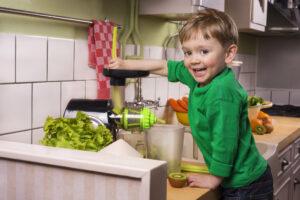 a boy making green juice