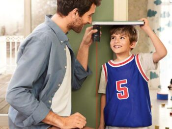 a father measuring the height of his son
