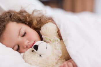a little girl sleeping with her teddy
