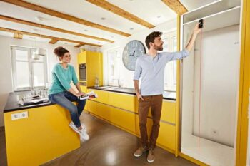 a man measuring the interior height of a cabinet
