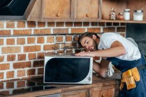 a repair man fixing a kitchen appliance