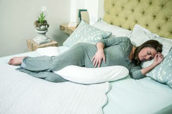 expectant mother sleeping on bed