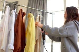 girl steams clothes on hanger