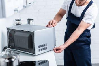 handyman checking kitchen appliance