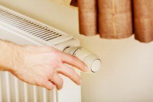 man adjusting heater temperature