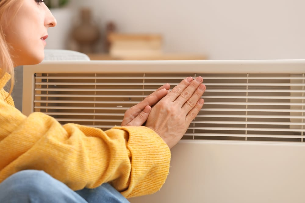 mature-woman-warming-hands-near-electric-heater-at-home-concept-of-heating-season