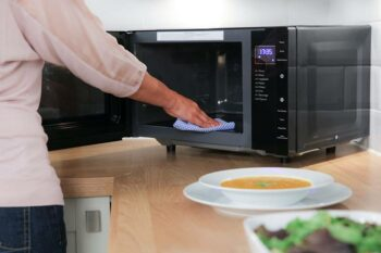 woman cleaning cooking appliance
