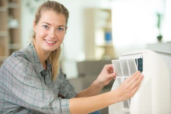 woman removing AC filter