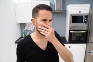 young man covers nose in smelly kitchen