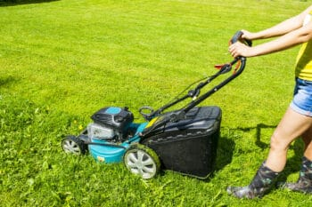 a woman mowing grass