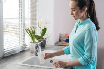 a-young-lady-filling-a-glass-of-water-in-the-tap