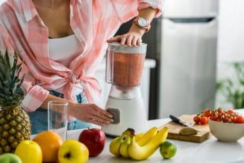 close-up of a woman making a shake at home