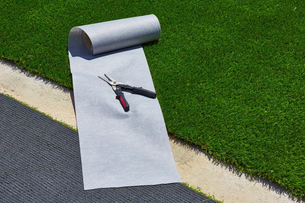 artificial-grass-turf-installation-in-garden-with-tools