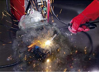 man wearing gloves to safely weld metal