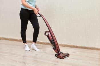 woman vacuuming the dust of te floor