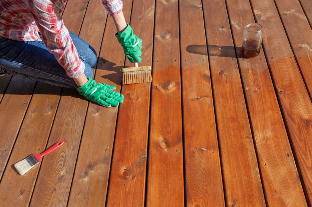 woman varnishing the wooden deck
