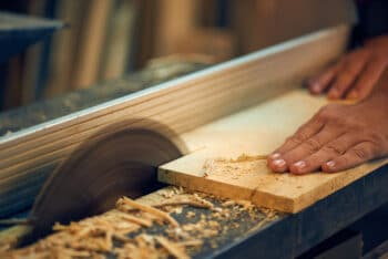 worker cutting wood in shop