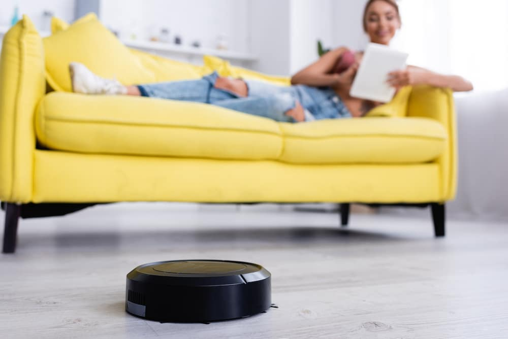 A woman unwinds on a couch while the robotic cleaner cleans the house