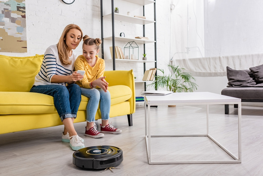 The mother demonstrates to her daughter how to use her smartphone to control the robotic cleaner